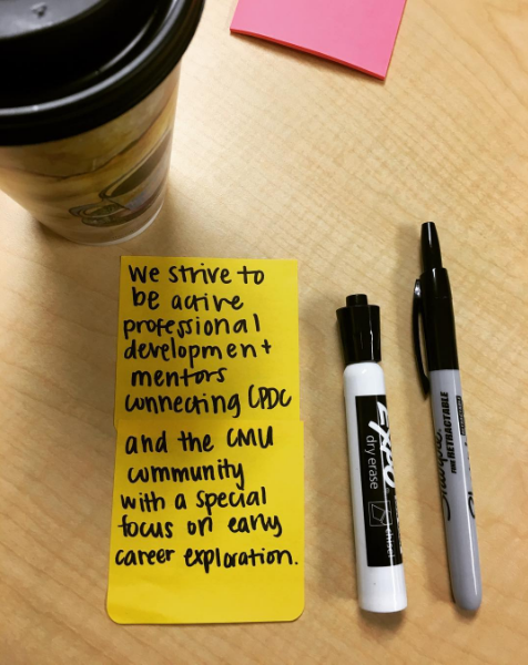 "The image of a mission statement on sticky notes next to two markers. The sticky notes read ""We strive to be active professional developmetn mentors connecting CPDC and the CMU community with a special focus on early caeer exploration."""