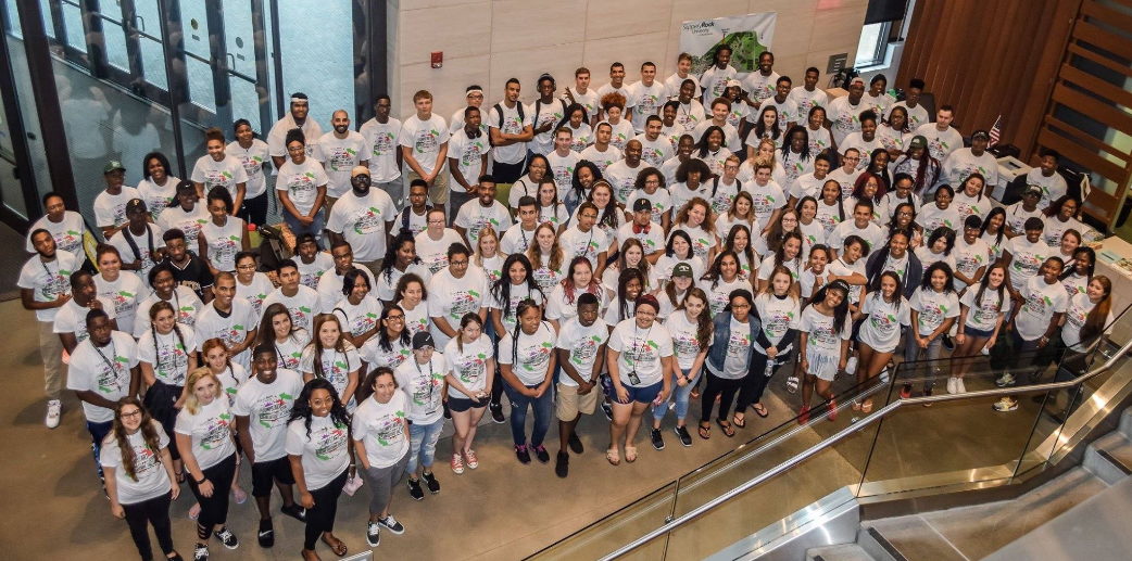 Photos of 100+ college students in the SRU Jump Start program. Birds eye view of students smiling in white t-shirts.