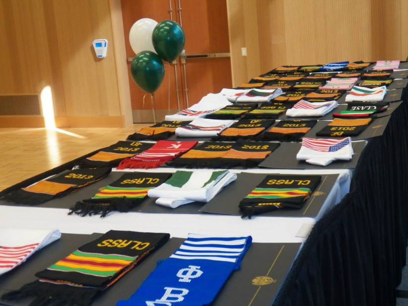 Photo of kente, NPHC Greek, and nationality stoles with graduation certificates upon a black clothed table.
